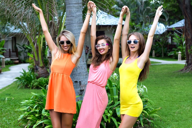 Retrato de verano de estilo de vida de amigos de la mujer de la compañía, divirtiéndose bailando y riendo en la zona del hotel, vacaciones de lujo en un país tropical exótico, vestidos brillantes y gafas de sol, estilo caribeño.