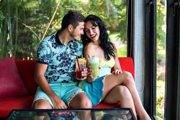Retrato de verano de un joven y una mujer disfrutan de su cita romántica, posando en un elegante café, bebiendo cócteles, divirtiéndose en la fiesta.
