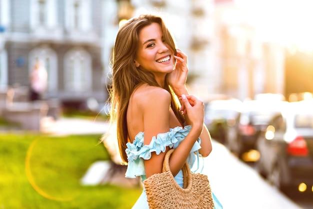 Retrato de verano de moda de estilo de vida de elegante joven modelo magnífico posando en la calle, luz del sol brillante de la tarde, elegante vestido azul femenino y bolso de paja, experiencia de viaje.