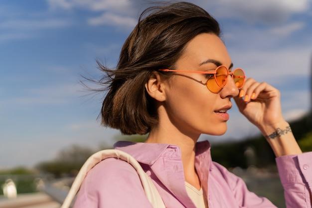 Retrato de verano de mujer de pelo muy corto con elegantes gafas de sol caminando al aire libre