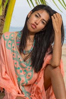 Retrato de verano de sonriente mujer bastante asiática en ropa de playa con estilo rosa sentado en la arena cerca de la palmera, océano azul. joyas, pulsera y collar.
