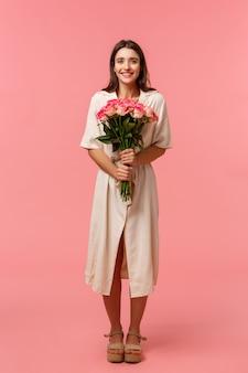 Retrato vertical de cuerpo entero atractivo, encantadora joven recibiendo hermosas flores, sosteniendo un ramo disfrutando de una cita romántica, sonriendo alegremente, de pie, pared rosada encantada