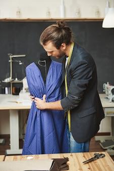 Retrato vertical del diseñador de moda hispano talentoso apuesto y varonil con cabello oscuro en traje de moda creando un vestido nuevo con maniquí, preparándose para el desfile