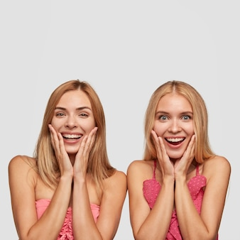 Retrato vertical de dos niñas alegres con amplias sonrisas, asombrado al ver algo increíble y agradable, parados uno al lado del otro