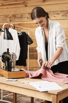 Retrato vertical de feliz entusiasta sastre mujer sonriendo mientras disfruta de su trabajo en el taller, cortando tela con unas tijeras, planeando coser en la máquina de coser nueva paz de la prenda.