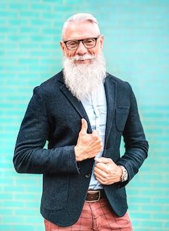 Retrato vertical de hombre hipster con elegante traje posando sobre fondo de pared turquesa