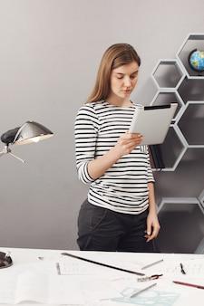 Retrato vertical de joven profeciaonnal atractiva chica arquitecta con cabello castaño en camisa a rayas y jeans negros de pie cerca de la mesa mirando en la mesa digital, mirando a través del cliente de la comisión
