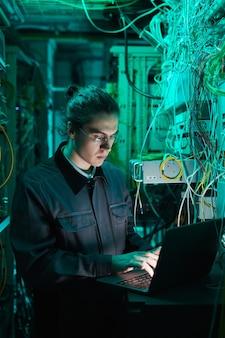 Retrato vertical de un joven técnico de redes con un portátil en la sala de servidores mientras configura la supercomputadora en el centro de datos