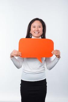 Retrato vertical de mujer joven alegre con discurso de burbuja roja sobre fondo blanco.