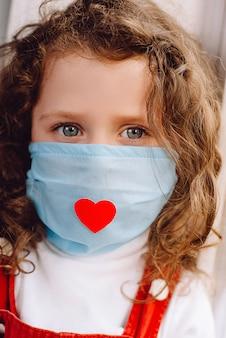 Retrato vertical recortado de una niña linda europea con una máscara de salud con un corazón rojo como una forma de mostrar agradecimiento y agradecer a todos los empleados esenciales durante la pandemia de covid-19.