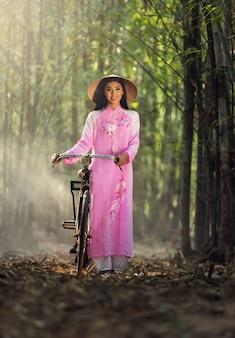Retrato de vestido tradicional vietnamita con bicicleta.