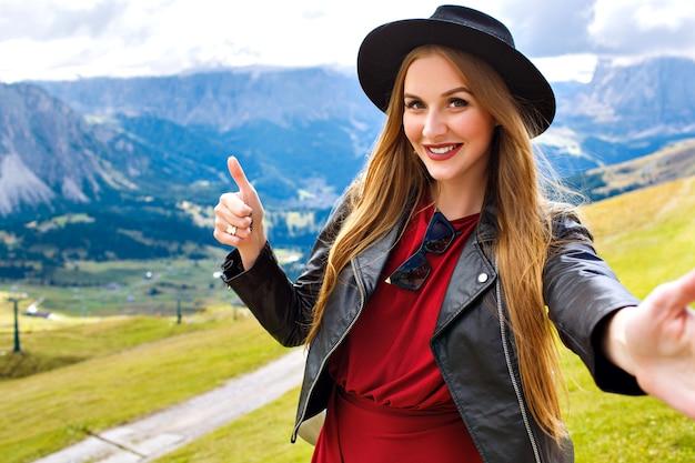 Retrato de viaje al aire libre de mujer turista joven bastante alegre