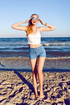 Retrato de viaje de estilo de vida al aire libre de joven rubia posando cerca del océano, top corto, mini denim hipster vintage shorty, mochila y gafas de sol, listo para aventuras, sexy cuerpo bronceado, piernas largas.