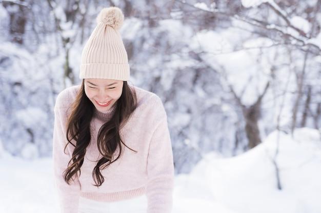 El retrato del viaje feliz de la sonrisa asiática hermosa joven de la mujer y goza con la estación del invierno de la nieve