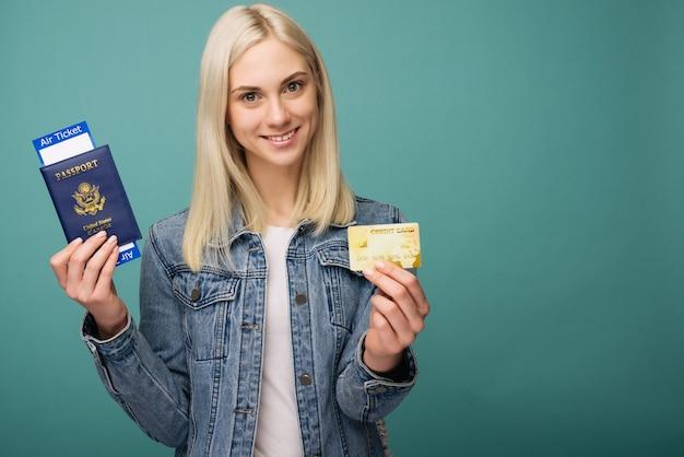 Retrato de un viajero alegre linda chica americana mostrando pasaporte con billetes de avión y tarjeta de crédito aislado sobre fondo azul.