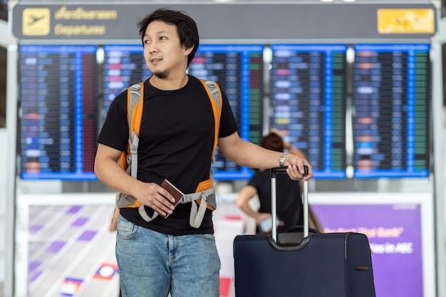 Retrato de viajero asiático con equipaje con pasaporte de pie sobre el tablero de vuelo