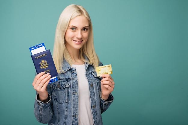Retrato de viajero chica americana mostrando pasaporte con billetes de avión y tarjeta de crédito