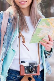 Retrato de un viajero femenino que sostiene la cámara y el mapa del vintage