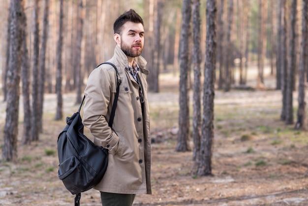 Retrato de un viajero masculino joven que sostiene la mochila en su hombro en el bosque