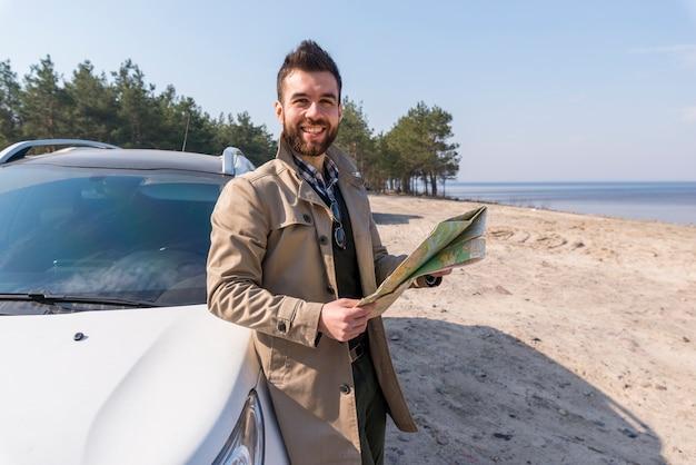 Retrato de un viajero masculino que se coloca cerca del mapa de la tenencia del coche en la mano que mira la cámara