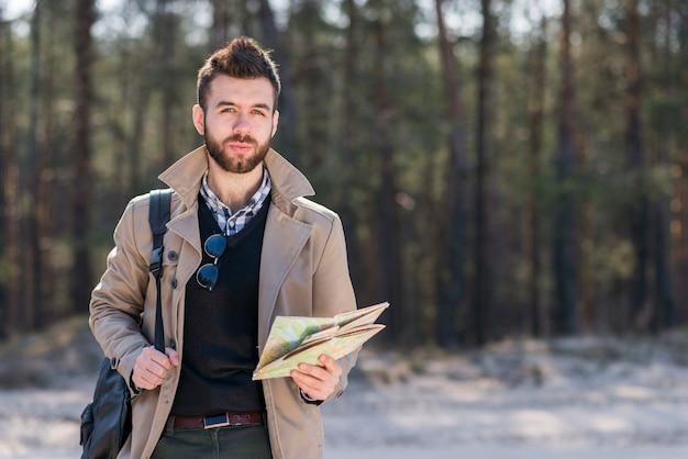 Retrato de un viajero masculino con su mochila en el hombro sosteniendo un mapa en la mano mirando a la cámara