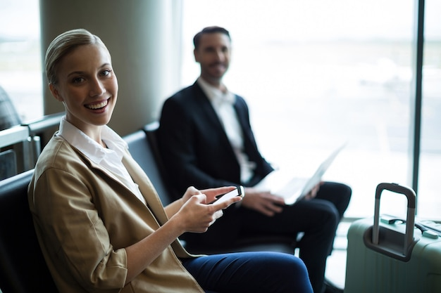 Retrato de viajeros sonrientes sentados en la sala de espera