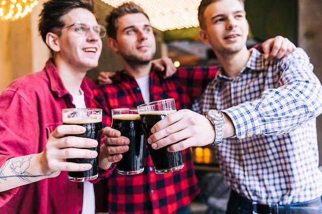 Retrato de los vidrios que tintinean del amigo masculino con la cerveza en pub