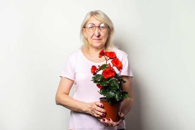 El retrato de una vieja mujer amistosa en una camiseta casual y los vidrios que sostienen una habitación florecen en una pared ligera aislada. cara emocional el concepto de cuidado de plantas, huerto familiar