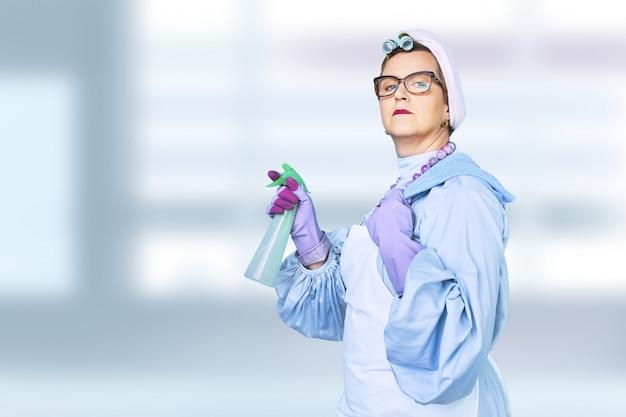 Retrato de la vieja señora de la limpieza en delantal con el cepillo de limpieza del polvo aislado en fondo azul. uniforme especial y equipo profesional para la limpieza.