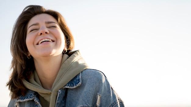 Retrato de vista baja de niña sonriente y cielo