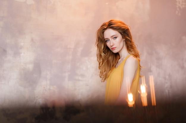 Retrato de la vista delantera de la mujer joven hermosa que desgasta contra la pared gris del desván.