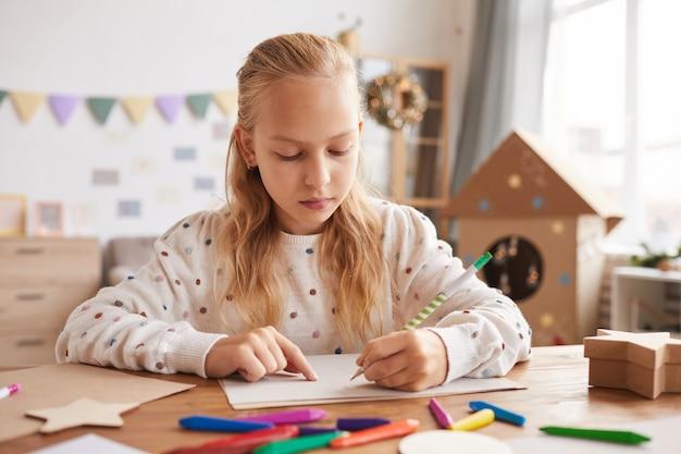 Retrato de vista frontal de una adolescente rubia dibujando o haciendo la tarea mientras está sentado en el escritorio en el interior de la casa, espacio de copia