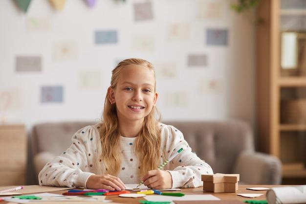 Retrato de vista frontal de una adolescente rubia sonriendo a la cámara mientras dibuja o hace la tarea sentado en el escritorio en el interior de la casa, espacio de copia