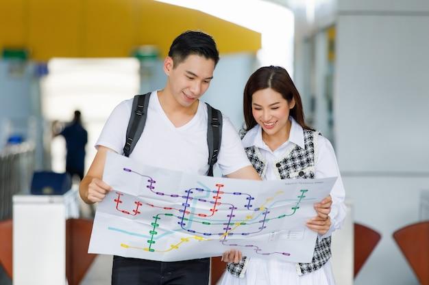 Retrato de vista frontal de los viajeros amantes asiáticos adultos jóvenes sonrientes lindos de pie y mirando el mapa de papel del metro en vacaciones encontrando formas de lugares turísticos con un fondo borroso de la estación de skytrain