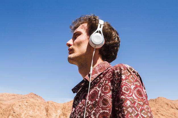 Retrato de vista inferior del hombre escuchando música en el desierto