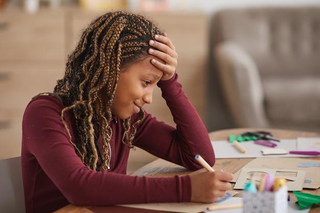 Retrato de vista lateral de una adolescente afroamericana dibujando con lápices mientras disfruta del arte y la artesanía en casa, espacio de copia
