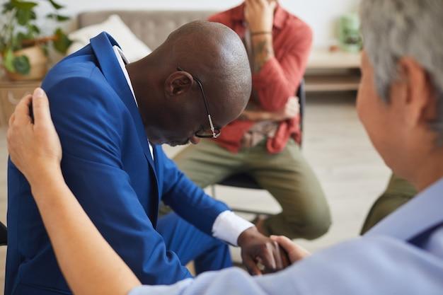 Retrato de vista lateral del afligido hombre afroamericano llorando en el grupo de apoyo con una mujer madura consolándolo, espacio de copia