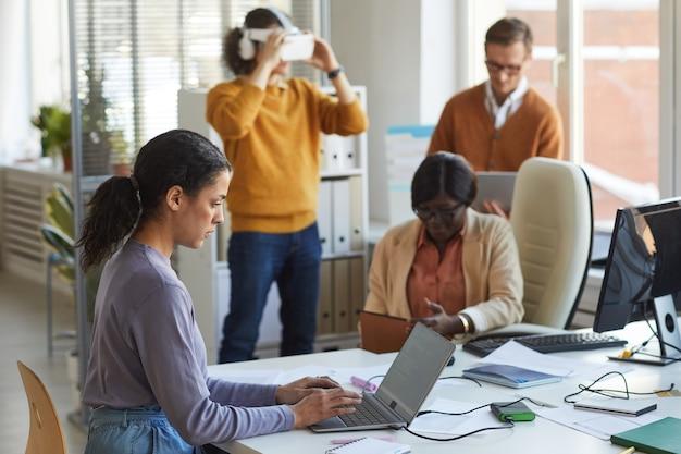 Retrato de vista lateral de la desarrolladora de ti femenina usando una computadora portátil con código en la pantalla mientras trabaja en el estudio de producción de software, espacio de copia