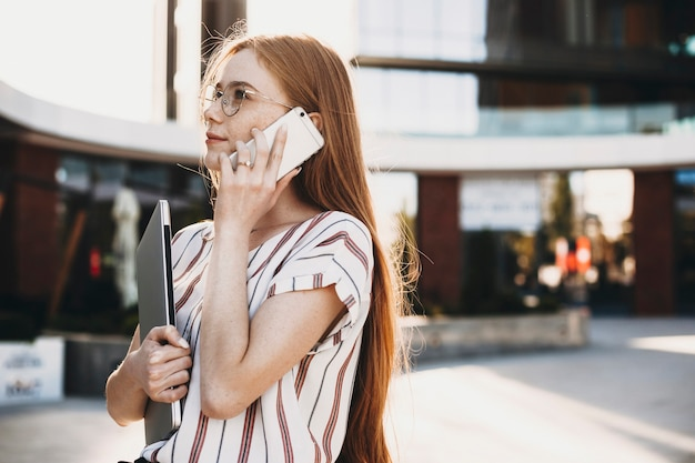 Retrato de vista lateral de una encantadora joven mujer de negocios hablando por el teléfono inteligente afuera contra un edificio mientras sostiene una computadora portátil.