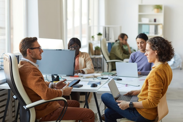 Retrato de vista lateral del equipo de jóvenes empresarios discutiendo el proyecto mientras trabajaba en el escritorio en el interior de la oficina blanca, espacio de copia