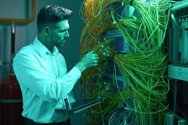 Retrato de vista lateral del guapo ingeniero de datos inspeccionando cables en la sala de servidores mientras trabaja con la supercomputadora en luz azul, espacio de copia