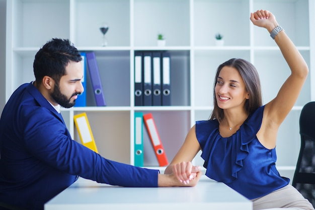 Retrato de vista lateral del hombre y la mujer armrestling, ejerciendo presión unos sobre otros