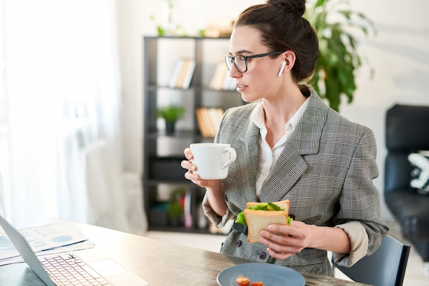 Retrato de vista lateral de la joven empresaria viendo videos a través de una computadora portátil durante el almuerzo en la oficina, copia espacio