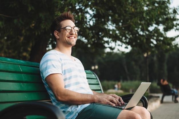 Retrato de vista lateral de un joven estudiante sentado en una playa mirando a otro lado riendo sosteniendo una computadora portátil en sus piernas después de las lecciones.