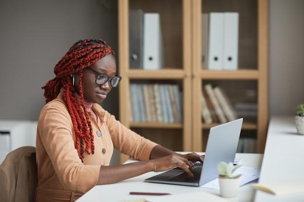 Retrato de vista lateral de la joven mujer afroamericana con ordenador portátil mientras estudia o trabaja desde casa en el lugar de trabajo, espacio de copia
