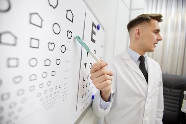 Retrato de vista lateral del joven oftalmólogo apuntando a la tabla de visión
