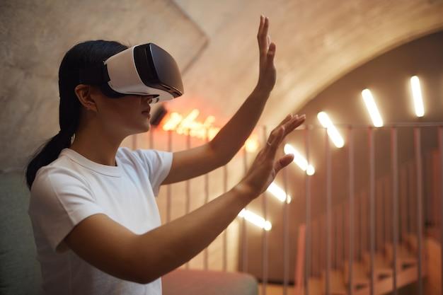 Retrato de vista lateral de una mujer asiática con equipo vr y gesticulando mientras disfruta de una experiencia inmersiva en un interior futurista
