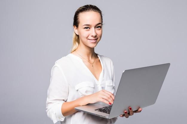 Retrato de vista lateral de una mujer joven alegre escribiendo en el portátil aislado en una pared gris