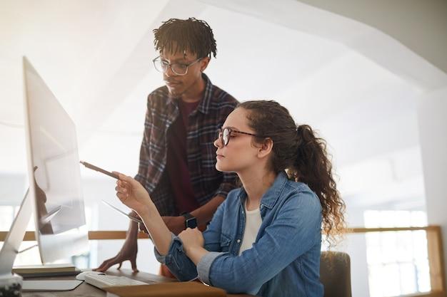 Retrato de vista lateral de una mujer joven contemporánea apuntando a la pantalla de la computadora mientras trabaja con un colega afroamericano en la oficina, concepto de desarrollador de ti femenino, espacio de copia