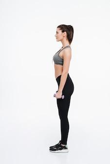 Retrato de vista lateral de una mujer joven de deportes de pie con pesas aislado en un fondo blanco